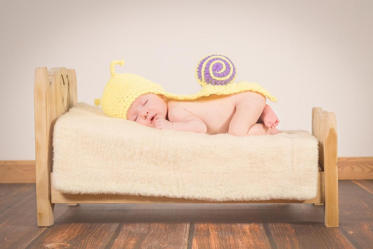 baby sleeping in wooden flooring room